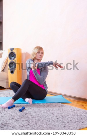 Female Training Ideas. Tranquil Mature Female While Exercising On Blue Mat During Session At Home. Vertical Image Stock photo ©
