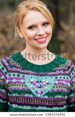 Female tramp walks in the park in a green hand-knitted Christmas sweater, pullover with a heart