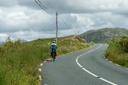 Female traveler cyclist pedaling in Connemara mountainous landscape Galway Ireland