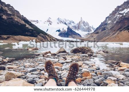 Female traveler in hiking boots having fun and enjoying wonderful breathtaking mountain view. Cerro Torre peak, Patagonia, Argentina. Travel trekking leisure holiday concept