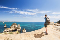 Female traveler looking at the sea in Lagos town, Algarve region, Portugal. Travel and active lifestyle concept
