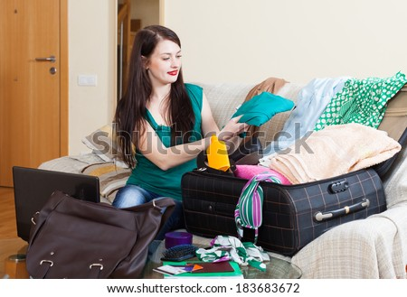 female traveler packing suitcase for holiday at home