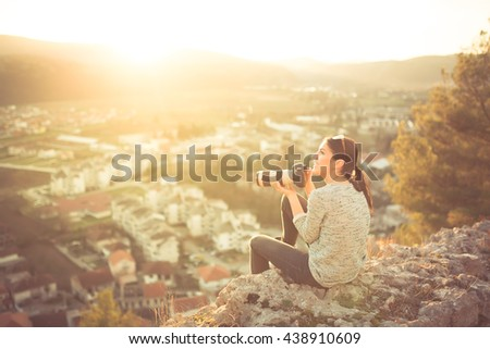 Female traveler photographer fascinated by illuminated nature at sunrise. Professional woman photographer taking outdoor portraits with telephoto lens. Taking break from job and enjoying the sunset.
