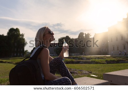 Female traveler sitting and enjoys the view of Wawel Castle with a bottle of water in the rays of sunlight. Krakow, Poland - Shutterstock ID 606502571
