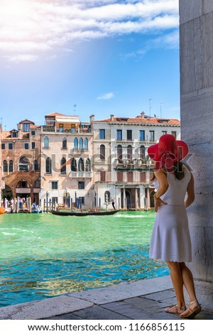 Female traveller woman enjoys the view to the architecture of the Canal Grande in Venice, Italy, on a sunny summer day #1166856115