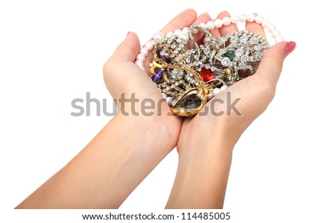 Female treasures. Necklaces, rings, earring in female hands isolated on white background. - stock photo