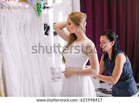 Female trying on wedding dress in a shop with women assistant. #621998417