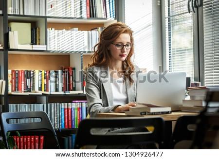 Female university professor preparing for class.She using laptop.