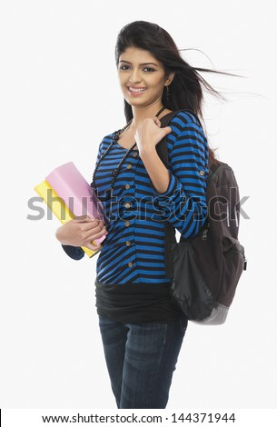 Female university student holding books and smiling