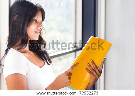 female university student reading book by the window