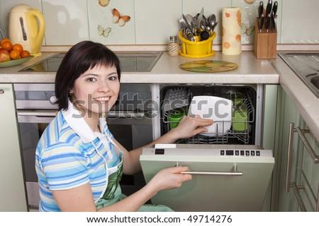 Female using dishwashing machine. Attractive brunette woman cleaning kitchen.