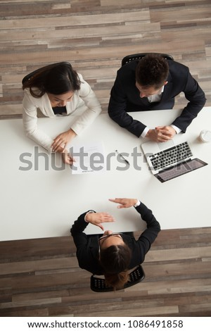 Female vacancy candidate answering questions at job interview talking to hr managers holding resume at office table, making good first impression, recruiting and hiring concept, top vertical view