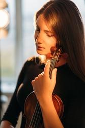 Female violinist portrait. Musical inspiration. Tranquility mind. Enjoying silence. Elegant smiling woman tenderly holding violin in hands warm lights.