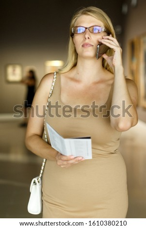 Female visitor with information booklet in her hands looking at exhibits and talking on phone in museum