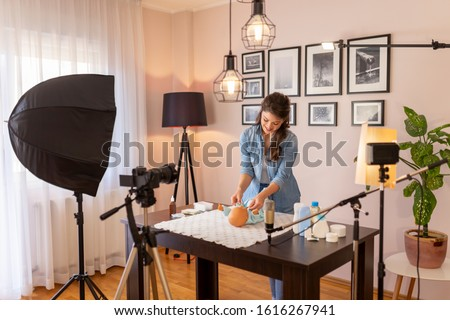Female vlogger filming video about changing newborn baby clothes as part of online prenatal classes course; female influencer recording tutorial about newborn baby care