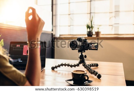 Female vlogger looking at camera while editing video on her laptop. Young woman working on computer with coffee and camera on her desk.