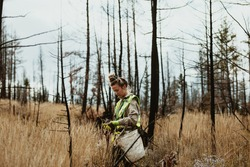 Female volunteer planting trees in forest. Woman tree planter wearing reflective vest walking in forest carrying bag full of trees and a shovel.