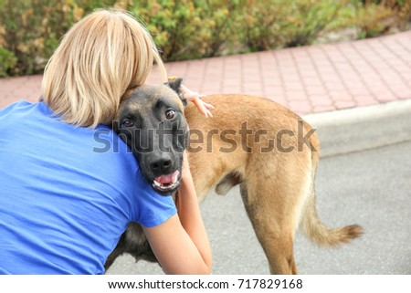 Female volunteer with homeless dog outdoors. Concept of volunteering and animal shelters #717829168