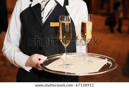 Female waiter welcomes guests with sparkling wine