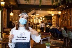Female waitress hanging open sign while reopening restaurant for delivery and takeaway only during coronavirus epidemic.  Woman holding sign we're open for takeaway orders only infront of restaurant.