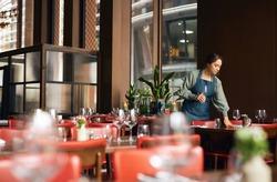 Female waitress setting tables in restaurant