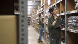 female warehouse worker checking stock of cables in stockroom. two asian chinese women coworkers standing and counting parcels in storehouse. young lady colleagues in uniform stock taking in depot.