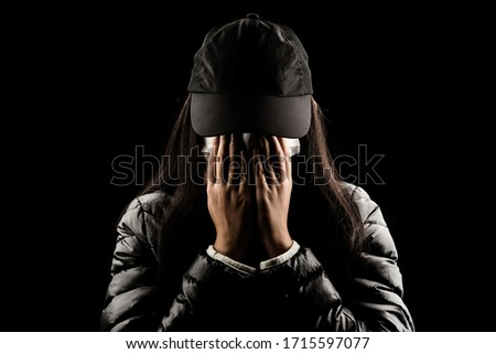 Female wear mask and hand covering face  sad crying on black background people worry unhappy protect virus carona covic 19