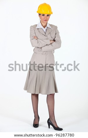 Female wearing a trench coat and a hardhat.