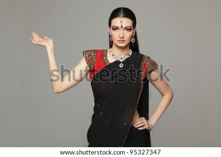 Female wearing sari presenting a product - empty copy space over grey background