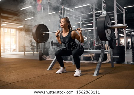 Female weightlifter is getting ready to stand with heavy barbell, squatting with weight, looking away with pleasant expression, enjoying training in gym, portrait, side shot