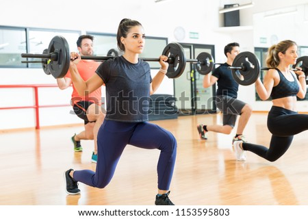 Female weightlifter lifting barbell while doing lunges with friends in health club