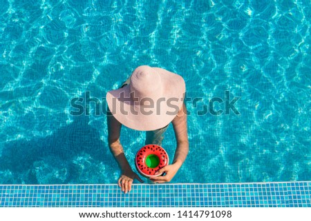 Female with a hat holding watermelon drink holder at swimming pool #1414791098