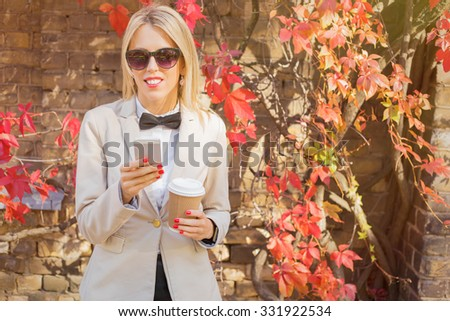 Female with coffee cup and phone in her hand #331922534