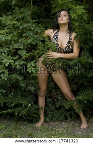 Female with dark hair posing in the bushes wearing a bathing suit