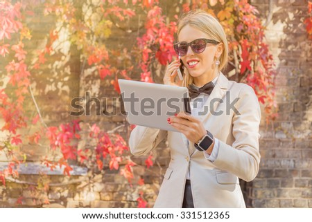 Female with tablet in her hands talking on the phone  #331512365
