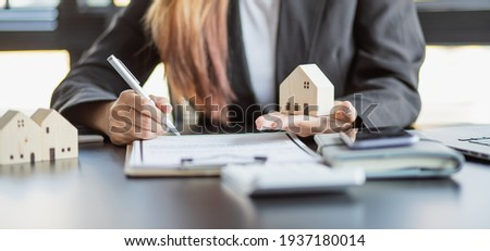 Female woman hands holding home model, small miniature white toy house. Mortgage property insurance dream moving home and real estate concept