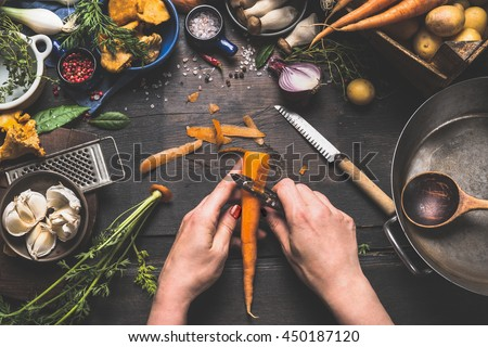 Female woman hands peeling carrots on dark wooden kitchen table with vegetables cooking ingredients, spoon and tools, top view