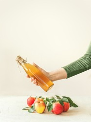 Female women hand holding bottle with homemade apple cider vinegar above table with apples and green leaves at white wall background. Apple season. Healthy fermented food concept