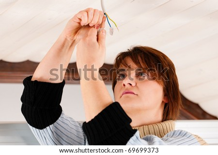 Female worker doing work on electrical installation