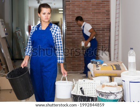 Female worker holding bucket of paint during decorating work in room
