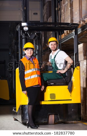 Female worker in vest and male worker in forklift at warehouse
