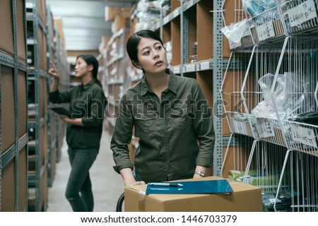 female worker in warehouse pushing cart with cardboard boxes. young woman staff putting clipboard on parcels and finding empty shelf to place goods. bokeh view of girl coworker doing stocktaking. #1446703379