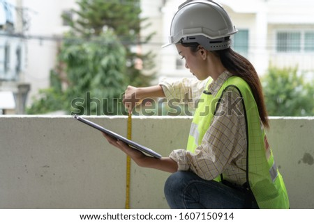 Female worker occupation. Woman inspector / architect checking interior material process in house reconstruction project.