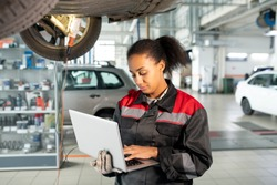 Female worker of car repair service in uniform using laptop in workshop to look for data in online sources, take new orders or consult clients