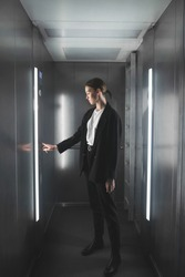 Female worker pressing the button in the elevator. Full-length portrait of a girl in the lift pressing the button.