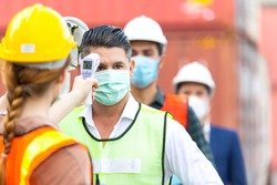 Female worker scanning fever temperature with digital thermometer to construction site staff wearing hygiene face mask protect from Coronavirus or COVID-19. New Normal working life adaptation in 2020