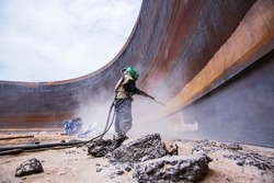 Female worker surface corrosion plate preparation by sand blasting of tank internal oil