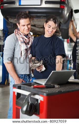 Female worker using laptop while standing next to client in garage with person in the background