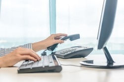 Female working, hands using computer telephone, closeup