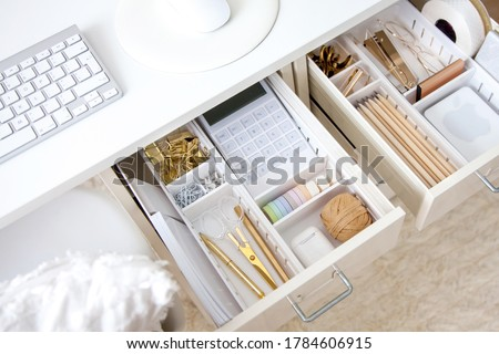 Female workplace. White work table. The stylish gold stationery is arranged very neatly in the drawers of the desk. Japanese storage method. Сток-фото ©